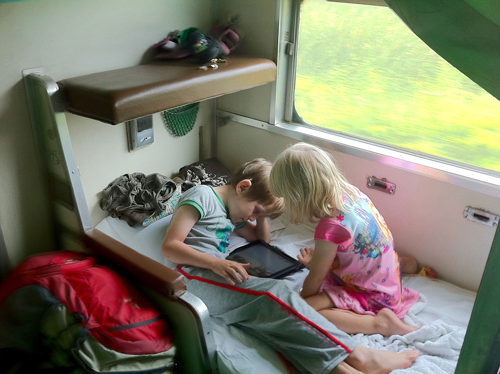 The kids enjoy the Second Class sleeper carriage while traveling through Bangkok, Thailand.